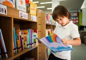 niño saca libros de la biblioteca