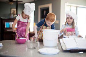 niños participando en la tarea de la cocina